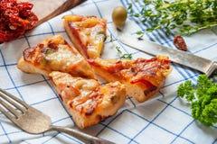 Corte redondo de Margarita de la pizza de salchicha en los pedazos para alimentar el paño con los tomates secados al sol Foco sel foto de archivo