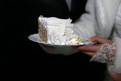 Corte un pedazo de pastel de bodas en las manos de la novia Imagen de archivo libre de regalías