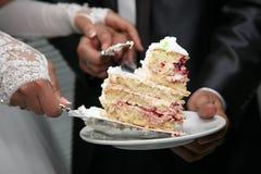 Corte un pedazo de pastel de bodas en las manos de la novia y del novio Imagenes de archivo