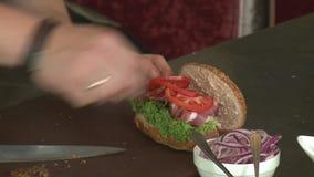 Corte un tomate con un cuchillo almacen de metraje de vídeo