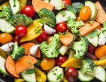 Corte vegetais crus sazonais - batatas doces, brócolis, pimentas de sino, abobrinha, tomates, cebolas, alho com especiarias e erv imagens de stock