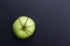 Corte verde de la manzana en la forma del gráfico de sectores en tablero trasero imágenes de archivo libres de regalías