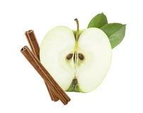 Corte verde de la mitad de la manzana con los palillos de canela aislados foto de archivo