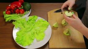 Cortes da mulher uma maçã verde com uma faca em uma placa de madeira filme