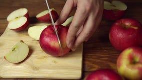 Cortes da pessoa uma maçã em fatias em uma placa de corte vídeos de arquivo