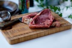 Cortes de la carne de vaca cruda en la tabla de cortar con un poco de ensalada verde en t Imágenes de archivo libres de regalías