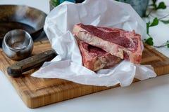 Cortes de la carne de vaca cruda en la tabla de cortar con un poco de ensalada verde en t Foto de archivo