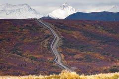 Cortes de la tubería de Alaska del transporte del aceite a través de la montaña rugosa Landsc Imagen de archivo