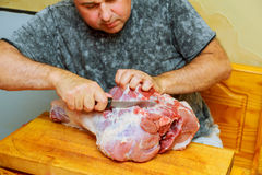 Cortes del hombre del pedazo de carne fresco en una tabla de cortar de madera la cocina casera Fotos de archivo libres de regalías