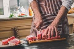 Cortes del hombre del pedazo fresco de carne de vaca en una tabla de cortar de madera en la cocina casera Fotos de archivo libres de regalías