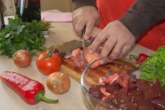 Cortes del hombre del pedazo de carne fresco en una tabla de cortar de madera en la cocina casera Fotografía de archivo libre de regalías