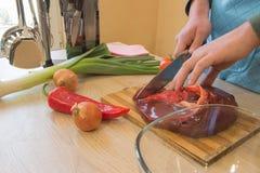 Cortes del hombre del pedazo de carne fresco en una tabla de cortar de madera en la cocina casera Foto de archivo