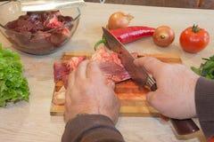 Cortes del hombre del pedazo de carne fresco en una tabla de cortar de madera en la cocina casera Fotos de archivo libres de regalías