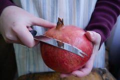 Cortes del hombre una granada madura con un knif foto de archivo