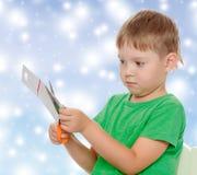 Cortes del muchacho con cartulina de las tijeras Fotos de archivo libres de regalías