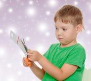 Cortes del muchacho con cartulina de las tijeras Imagenes de archivo