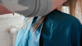 Cortes del peluquero con las tijeras el pelo recto mojado femenino en salón de belleza almacen de metraje de vídeo