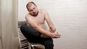 Cortes do homem seu close-up das unhas do p? Um homem faz-se um pedicure em casa no assoalho video estoque