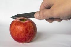 Cortes do homem uma maçã vermelha com uma faca foto de stock royalty free