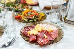 Cortes fríos de la carne en una tabla de banquete Fotografía de archivo libre de regalías