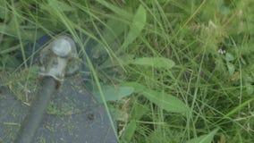 Cortes rotatorios hierba y ramas de la cuchilla eléctrica del condensador de ajuste en el sitio metrajes