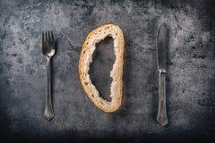 Corteza de la bifurcación del pan y cuchillo en tablero concreto Imagen entonada imagen de archivo libre de regalías
