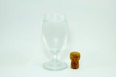 Cortiça do vidro e do champanhe de vinho no fundo branco imagem de stock