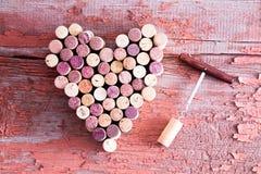 Cortiça na forma do coração e abridor de garrafa na tabela Fotos de Stock