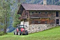 Cortijo de madera abandonado en una cuesta herbosa con el tractor rojo Imágenes de archivo libres de regalías