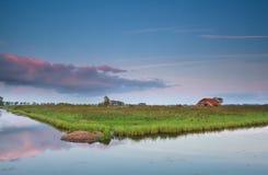 Cortijo holandés por el río en la puesta del sol Foto de archivo