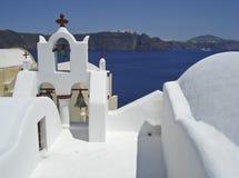 Cortile bianco della chiesa su un fondo del mare e del cielo (Santorini, Grecia) Fotografia Stock