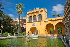 Cortile con lo stagno di acqua dell'alcazar, Siviglia, Spagna Fotografie Stock Libere da Diritti