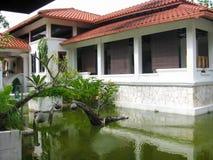 Cortile con lo stagno e la casa bianca sotto il tetto di mattonelle immagine stock