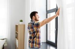 Cortina de janela da abertura do homem novo em casa imagem de stock