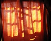 Cortina de ventana iluminada por el sol fotos de archivo