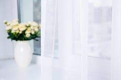 Cortina e flores brancas do algodão na janela fotografia de stock royalty free