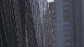 Cortina gris transparente en la ventana por la mañana, tocada suavemente por el viento La visión desde la ventana en la ciudad almacen de video