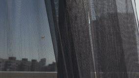 Cortina gris transparente en la ventana por la mañana, tocada suavemente por el viento La visión desde la ventana en la ciudad almacen de metraje de vídeo