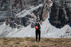 Cortina, Italia - giugno 2016: Il giovane scalatore ammira le alpi italiane il paesaggio delle dolomia ed il panorama di contamin Fotografie Stock