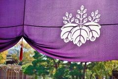 Cortina japonesa púrpura del templo con el emblema histórico del clan de Toyotomi Foto de archivo
