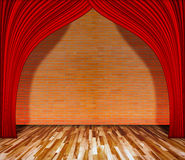 Cortina roja delante de la pared de ladrillo con el piso de madera Fotografía de archivo