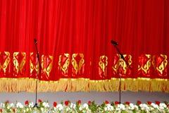 Cortina vermelha teatral de veludo com teste padrão do ouro, e os microfones foto de stock royalty free