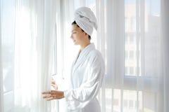 Cortinas asoleadas del blanco de la ventana de la mujer de la albornoz Foto de archivo libre de regalías