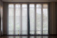 Cortinas blancas en el piso de madera imagenes de archivo