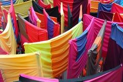Cortinas coloridas da tela nos suportes fotos de stock