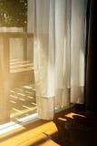 Cortinas completas brancas com luz solar brilhante e o assoalho de madeira Fotos de Stock