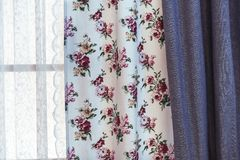 Cortinas con el estampado de flores en la ventana de la sala de estar fotos de archivo libres de regalías