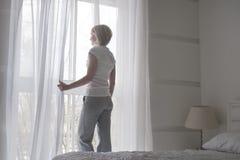 Cortinas de abertura bonitas novas da menina na manhã para obter o ar fresco, vista traseira Fotografia de Stock Royalty Free