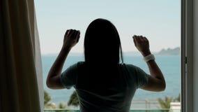Cortinas de abertura de la mujer joven en un dormitorio Vista del mar, de palmeras y de montañas a través de la ventana almacen de metraje de vídeo