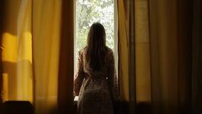 Cortinas de abertura de la mujer joven en un dormitorio en la mañana Ella que mira a través metrajes